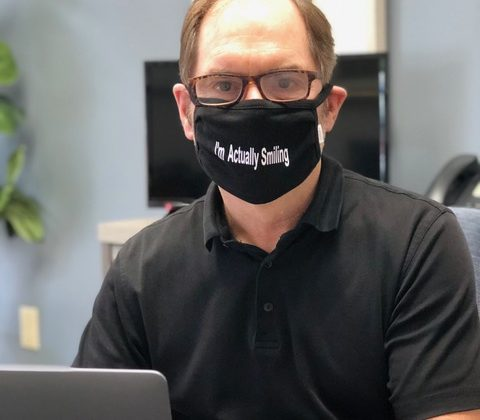 "Man wearing mask with message. ""I'm Actually Smiling""."